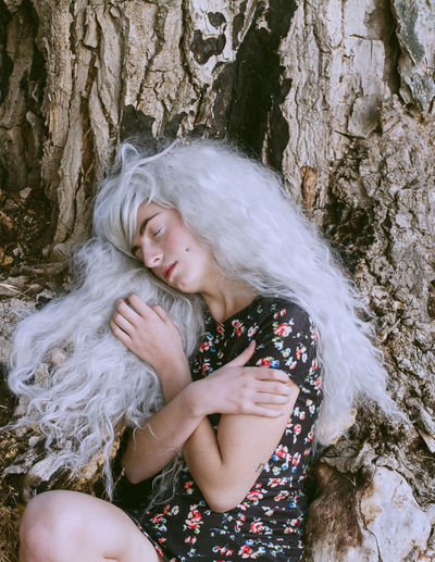 Man in dress and gray wig sleeping in forest