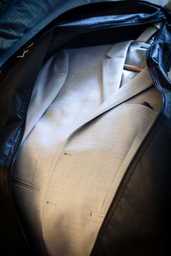 Grey suit jacket in garment bag laid out on a bed Close-up Clothing Garment Bag Grey Indoors  Jacket Light Grey No People Sport Coat Suit Suit Jacket Tuxedo Jacket First Eyeem Photo