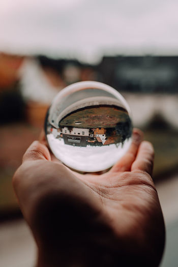 Crystal Globe Human Hand Hand Human Body Part Holding Unrecognizable Person One Person Real People Human Finger Finger Selective Focus Close-up Body Part Focus On Foreground Glass - Material Nature Personal Perspective Day Sphere Sky Outdoors Crystal Globe Globe Crystal Home Warm Clothing