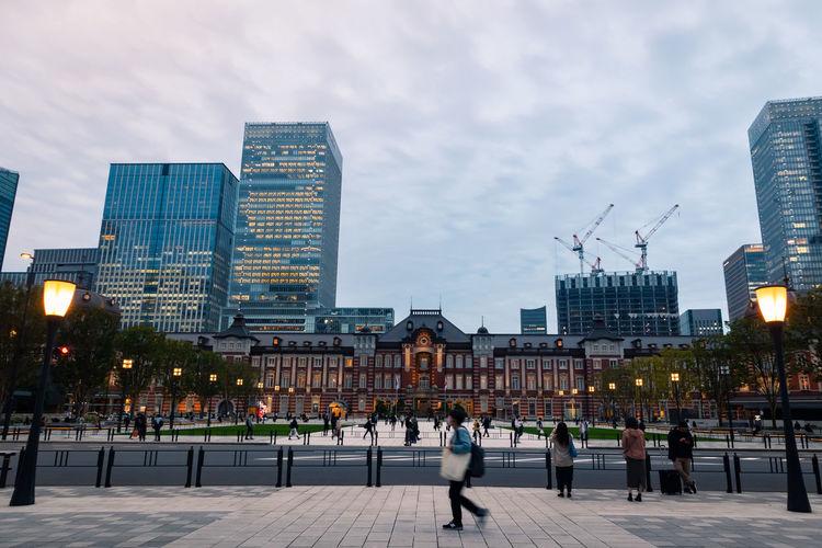 People walking on footpath by buildings in city against sky