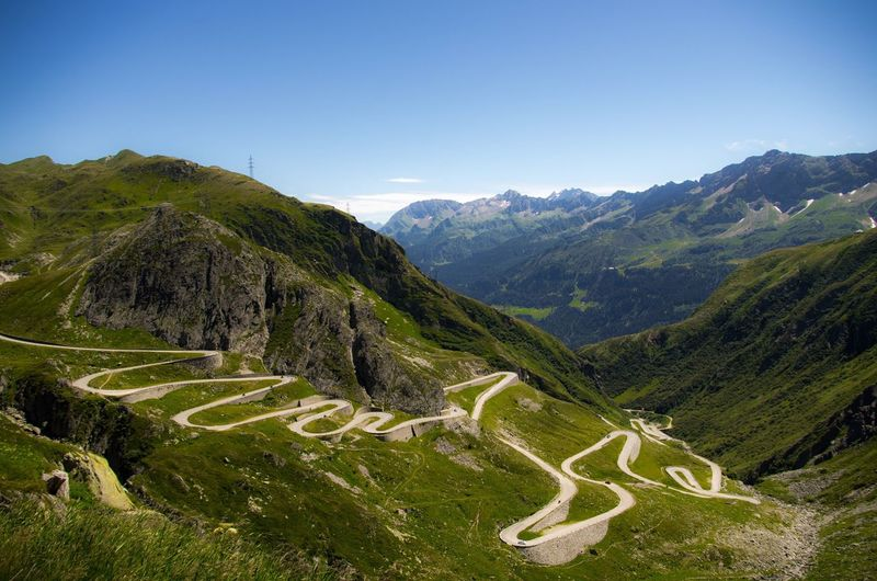High angle view of winding road against blue sky