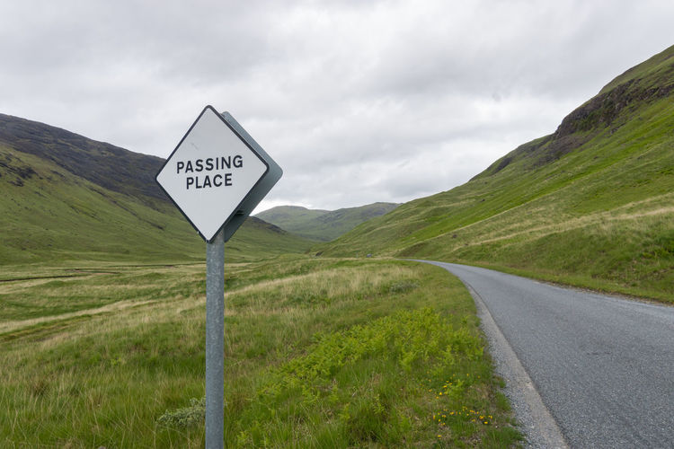 Road sign by mountains against sky