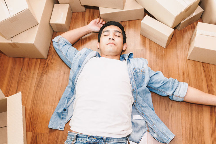 Man working overload and sleep near cardboard boxes around Beginnings Box Box - Container Cardboard Cardboard Box Casual Clothing Flooring Front View Hands Behind Head Hardwood Floor High Angle View Home Interior Home Ownership Indoors  Lifestyles Lying Down Lying On Back Moving House One Person Packing Parquet Floor Wood Young Adult Young Men
