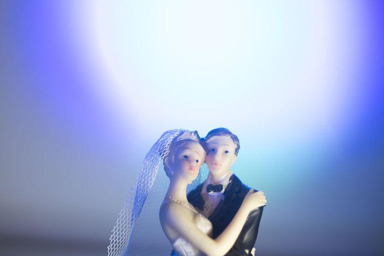 Portrait of couple kissing against blue sky