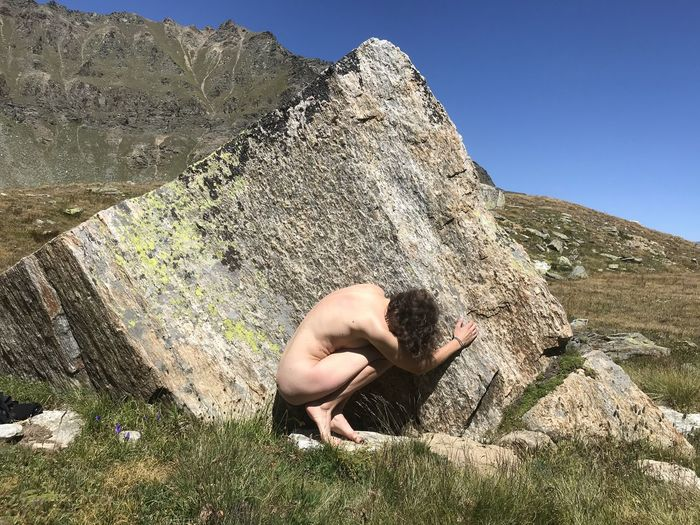 Young naked woman among the rocks in the mountains. alps and female nudity.