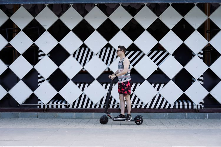 Full length of man riding push scooter against patterned wall