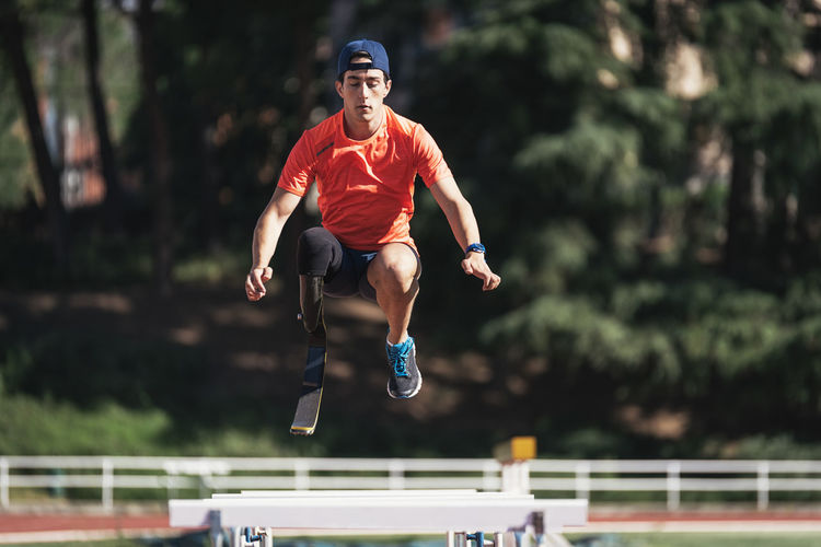 Young athlete with prosthetic leg jumping above railings at running track