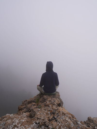 Rear view of person sitting at the edge of cliff during foggy weather