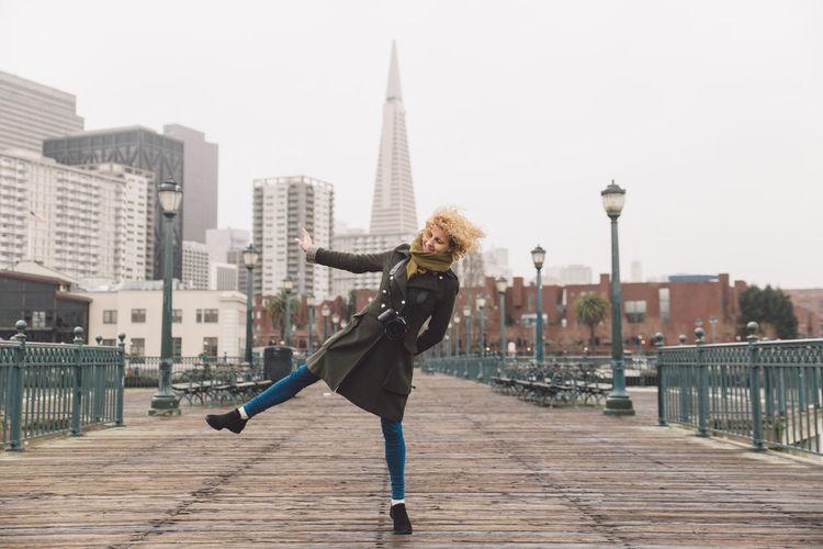 Woman dancing on bridge against buildings in city