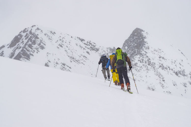 Rear view of hikers at snowcapped mountain against clear sky