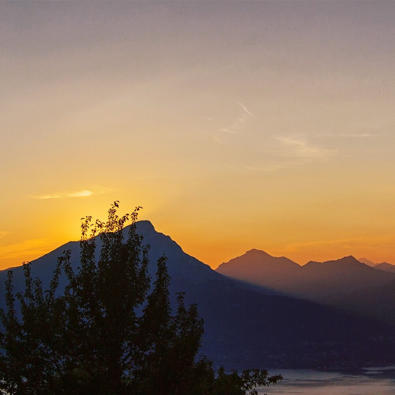 sunset, beauty in nature, nature, scenics, mountain, tranquility, tranquil scene, silhouette, no people, tree, outdoors, water, sky, mountain range, bird, animal themes, day