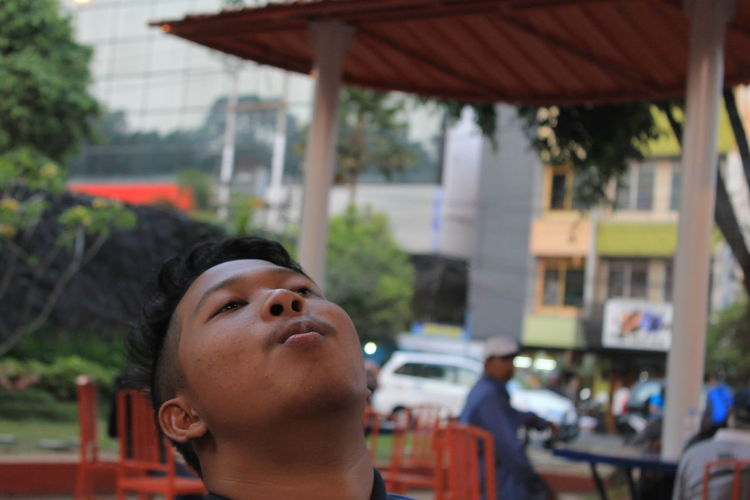 Close-up of man exhaling smoke at cafe