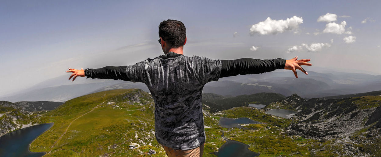 Rear View Of Young Man With Arms Outstretched Standing On Mountain Against Sky