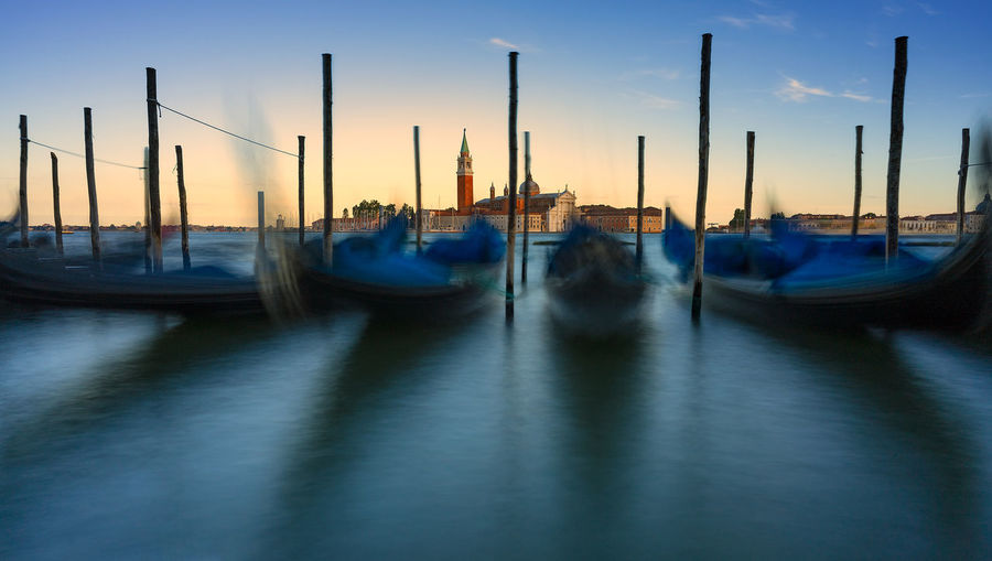 Boats moored by wooden post on canal against sky during sunset