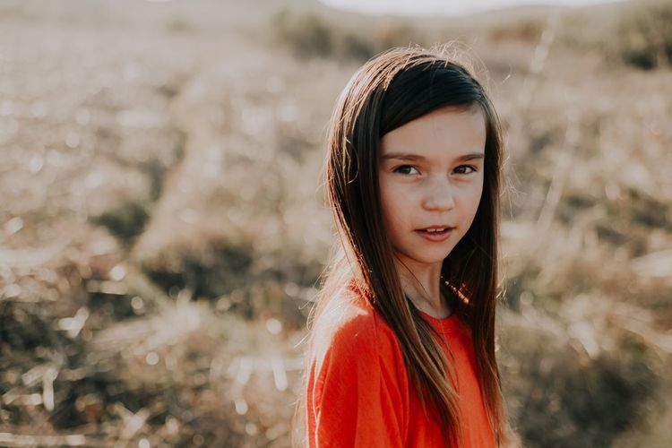 Portrait of cute girl with long hair standing on field