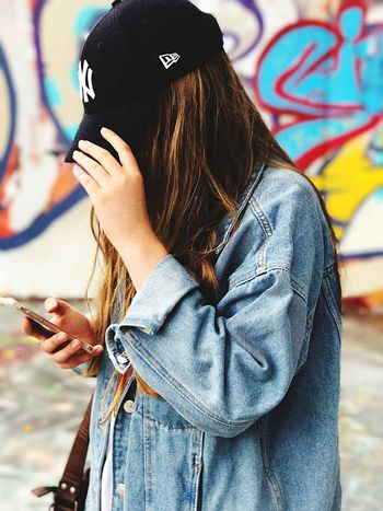 EyeEm Selects Wireless Technology Mobile Phone Portable Information Device Smart Phone Communication Technology Real People Text Messaging Using Phone Leisure Activity One Person Lifestyles Holding Casual Clothing Women Addiction Day Outdoors People Adult