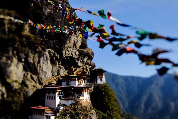Landscape of Paro Taktsang (Tiger Nest) in Upper Paro Valley, Bhutan. Taktsang Lhakhang is Bhutan most iconic landmark and religious site. foreground prayer flag five color. focus only temple Taktsang Architecture Belief Bhutan Building Building Exterior Built Structure Day Famous Place Flag Landmark Landscape Mountain Nature No People Outdoors Place Of Worship Religion Selective Focus Shrine Sky Spirituality Tourism Travel Destinations