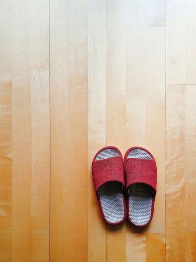Close-up of footwear on wooden floor