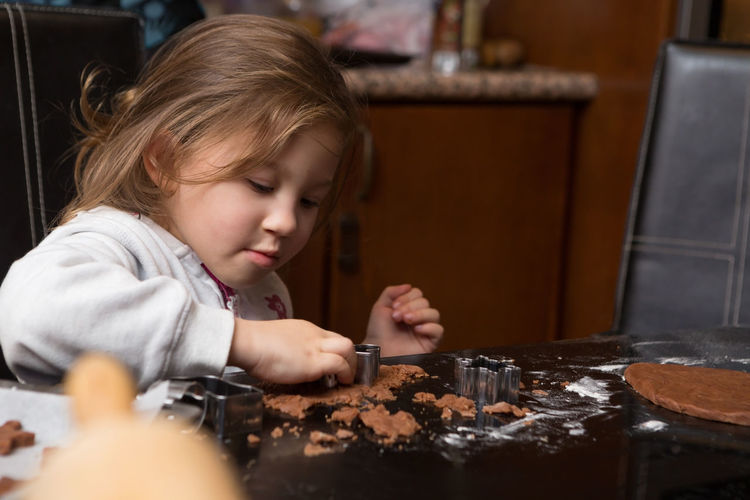 Girl preparing cookie on kitchen island at home