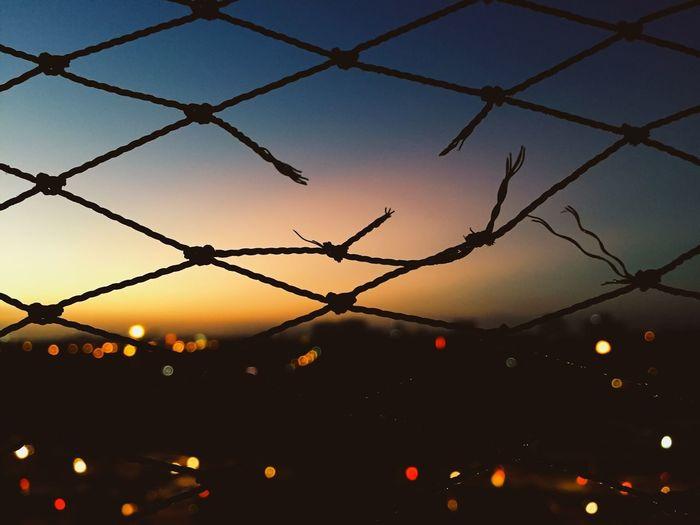 Full Frame Shot Of Broken Fence Against Sky During Sunset