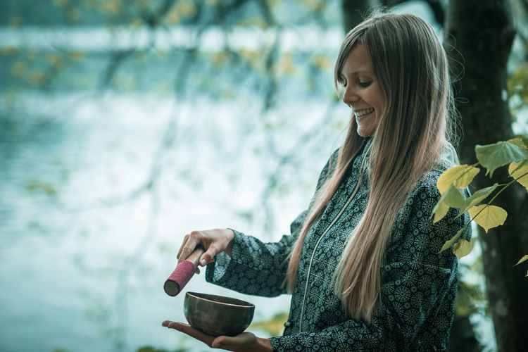 Smiling Young Woman Holding Bowl By Lake