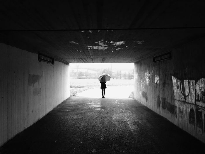 Rear View Of Woman Standing With Umbrella In Tunnel