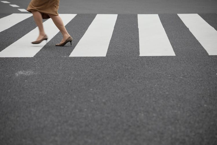 One Person Road Symbol Sign Road Marking Day Marking Body Part City Real People Low Section Human Body Part Human Leg Transportation Walking Women Lifestyles Street Standing Outdoors Human Limb Surface Level Crosswalk