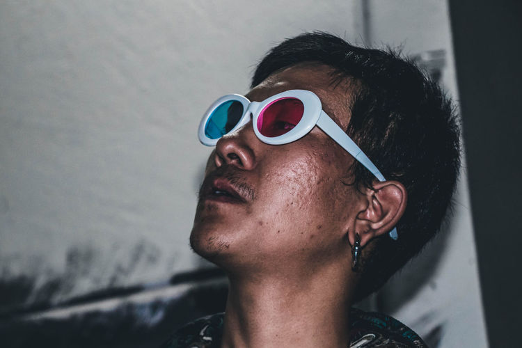 Young man wearing 3-d glasses while smoking cigarette