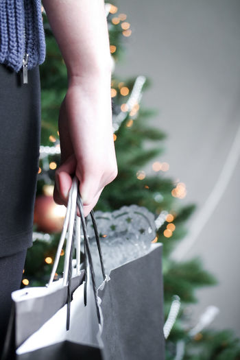 Cropped image of woman holding shopping bag while standing against christmas tree