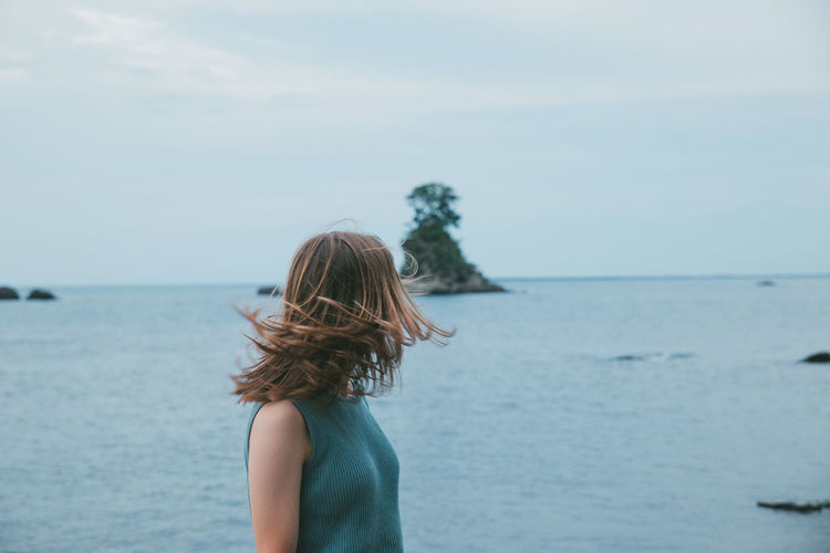 Woman tossing hair standing by sea against sky