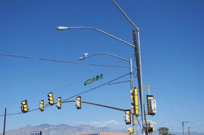 Low angle view of street lights and traffic signal against clear blue sky