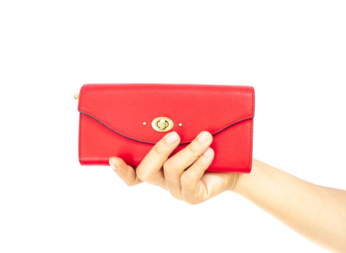Close-up of cropped hand holding red purse over white background