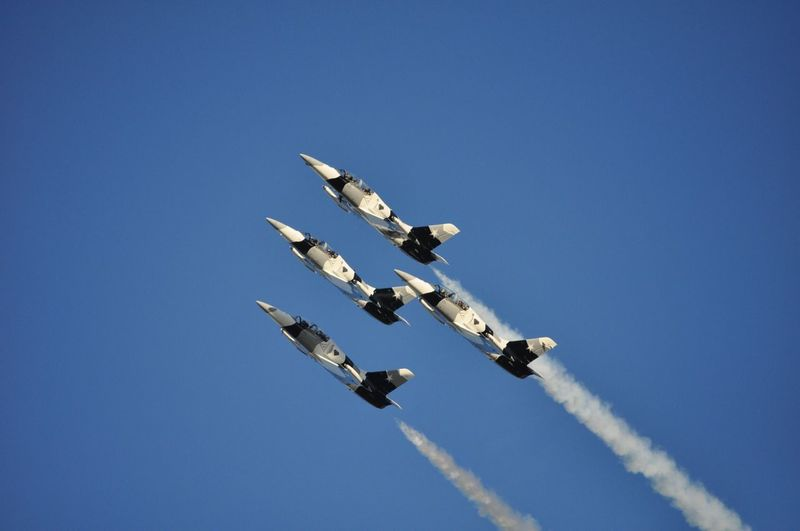 Low angle view of military aircrafts with trails against clear blue sky
