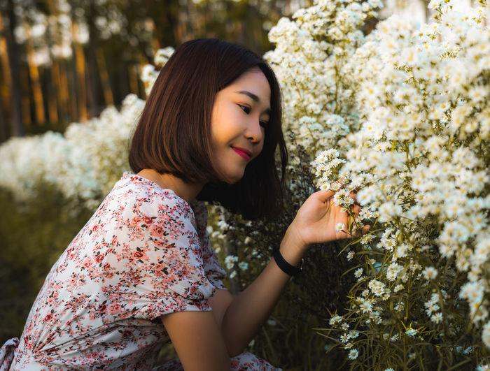 Portrait of beautiful woman against white flowering plants