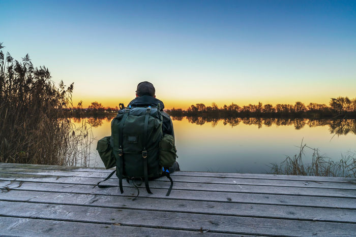Resting an watching the sun set Adult Backpack Beauty In Nature Full Length Grouse Lake Nature One Man Only One Person Outdoors Rear View Rucksack Sitting Sky Sky And Clouds Sunset Tree Water