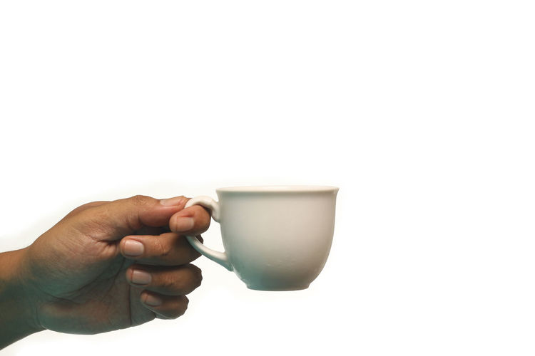 Midsection of person holding coffee cup against white background
