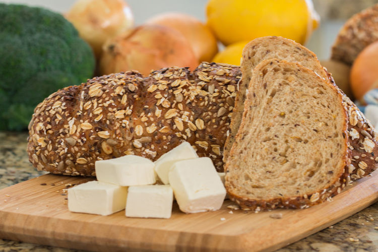 Whole wheat bread on wooden cutting board. Artisan; Background; Baguette; Bake; Baker; Bakery; Board; Bread; Breakfast; Brown; Butter; Cheese; Closeup; Cream; Crust; Cut; Cutting; Diet; Dough; Eating; Flour; Food; Fresh; Freshness; Gourmet; Grain; Healthy; Homemade; Kitchen; Loaf; Macro; Meal; Mul