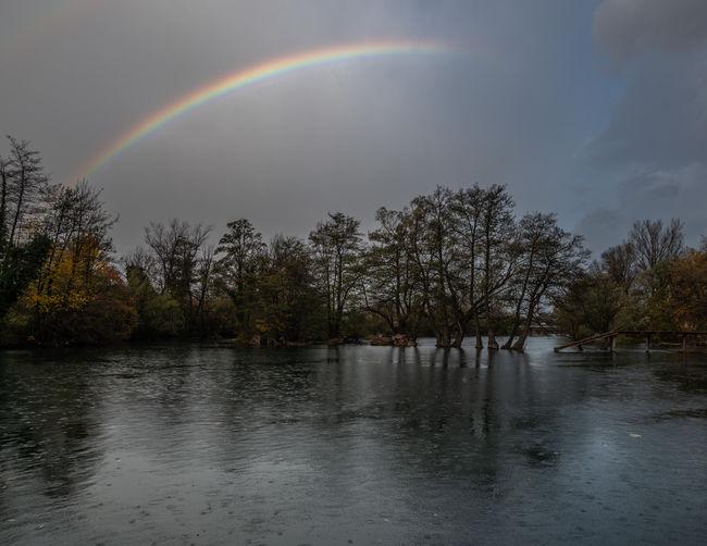 Scenic view of rainbow over lake during rainy season