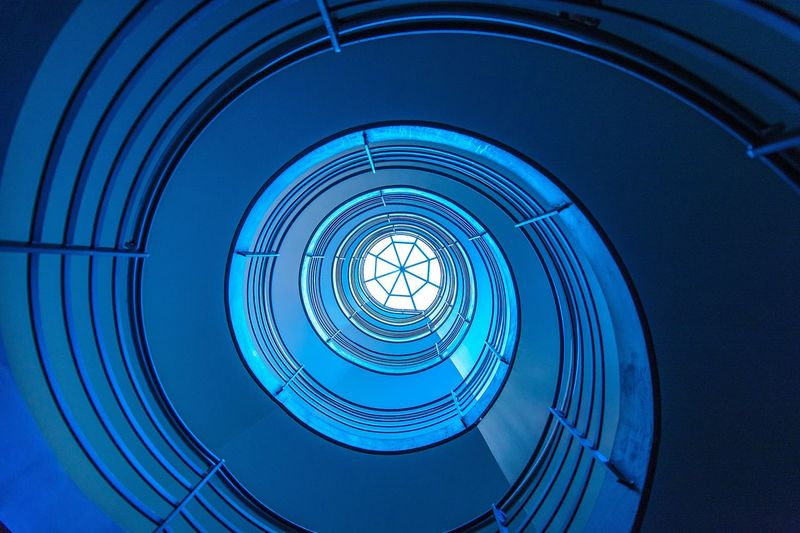 Directly Below Shot Of Spiral Staircase Against Skylight