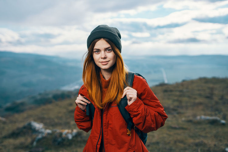 Portrait of beautiful young woman standing against sky during winter