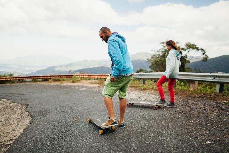 Couple skateboarding on road against sky