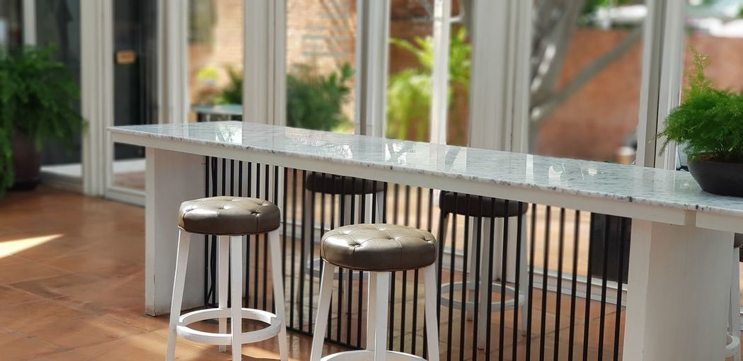 Stool chairs beside the white table and glass window Table Bar Prison Security Bar Radiator Arts Culture And Entertainment Metal Close-up Prison Bars