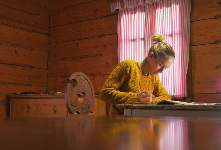 female artist painting a picture with watercolour in a cozy wooden cabin ArtWork Artist At Home Creativity Females Illustrator Pain Student Woman Working Abstract Brush Cabin Cottage Cozy Creative Diminishing Perspective Drawing Handmade Illustration Indoors  Lodge Painting Real People Table