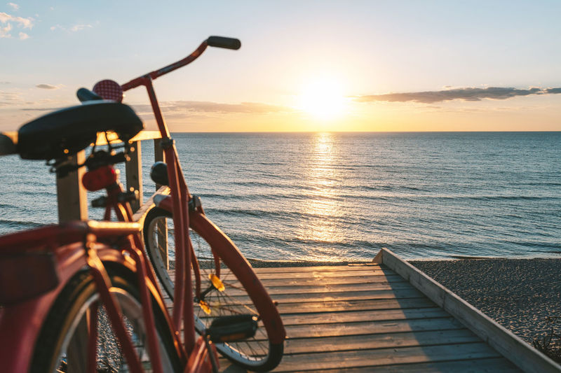 Bicycle by sea against sky during sunset