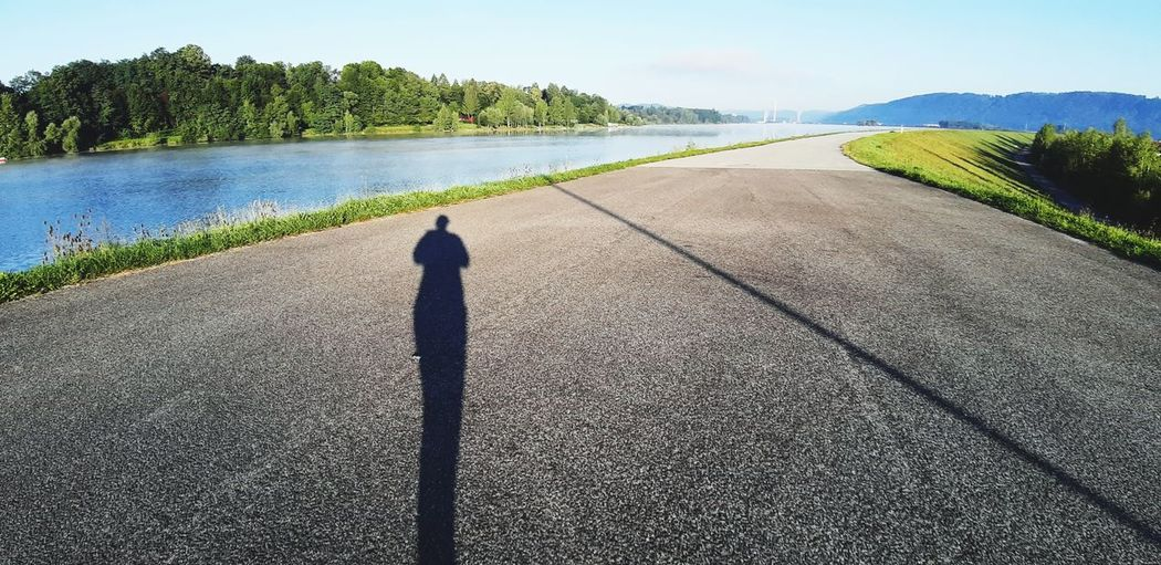 Shadow of woman standing on road against sky