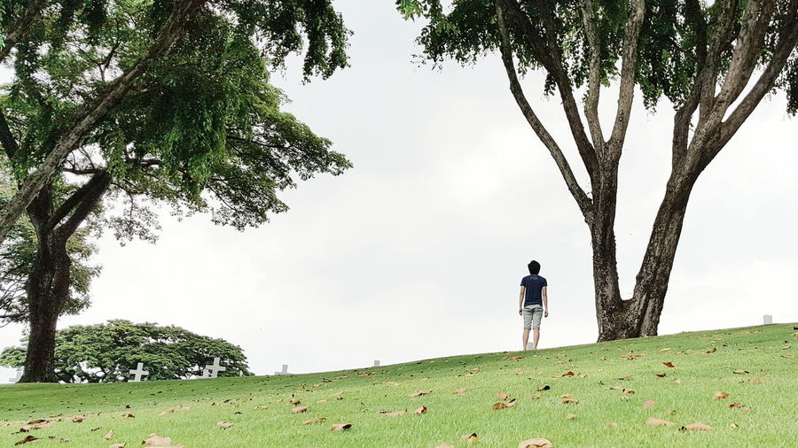 Rear View Of Man Standing By Cemeteries On Hill Against Sky
