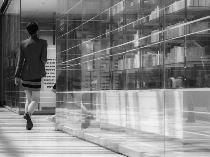 Full length of woman walking on glass window