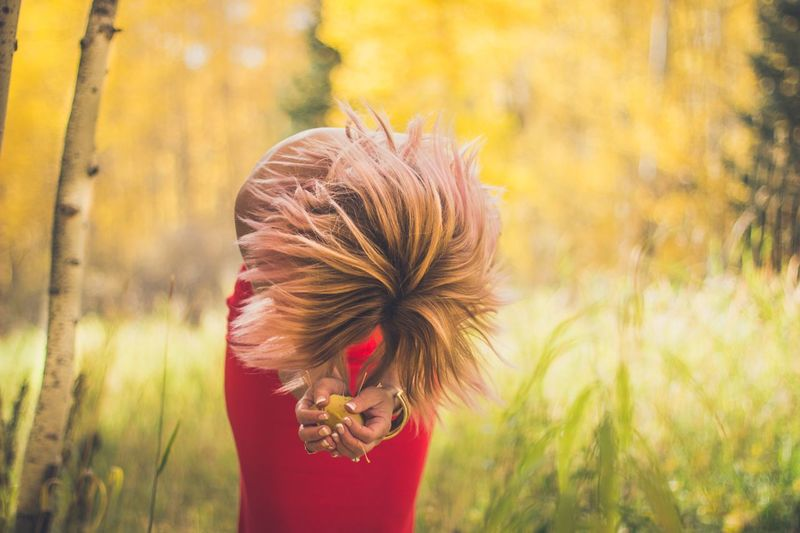 Woman With Blond Hair Holding Leaves While Bending At Forest