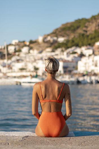 Rear view of woman wearing bikini looking at sea