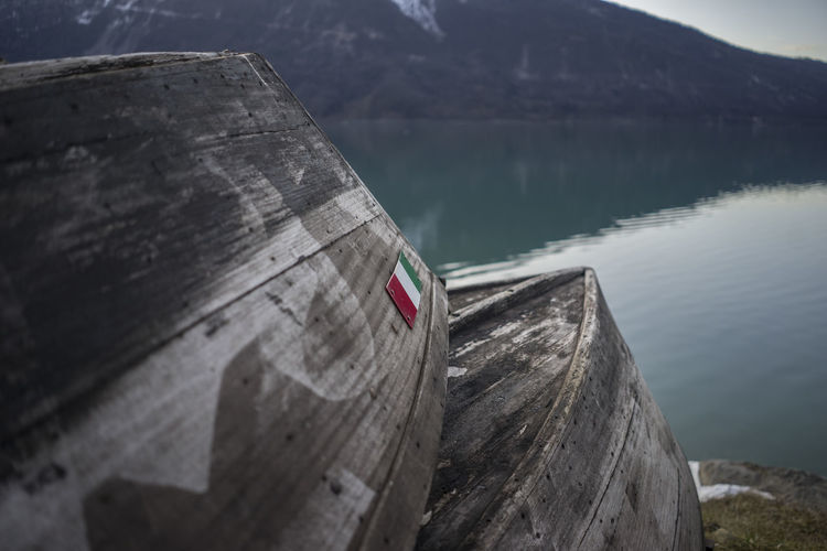 Wooden boats moored at riverbank against mountain